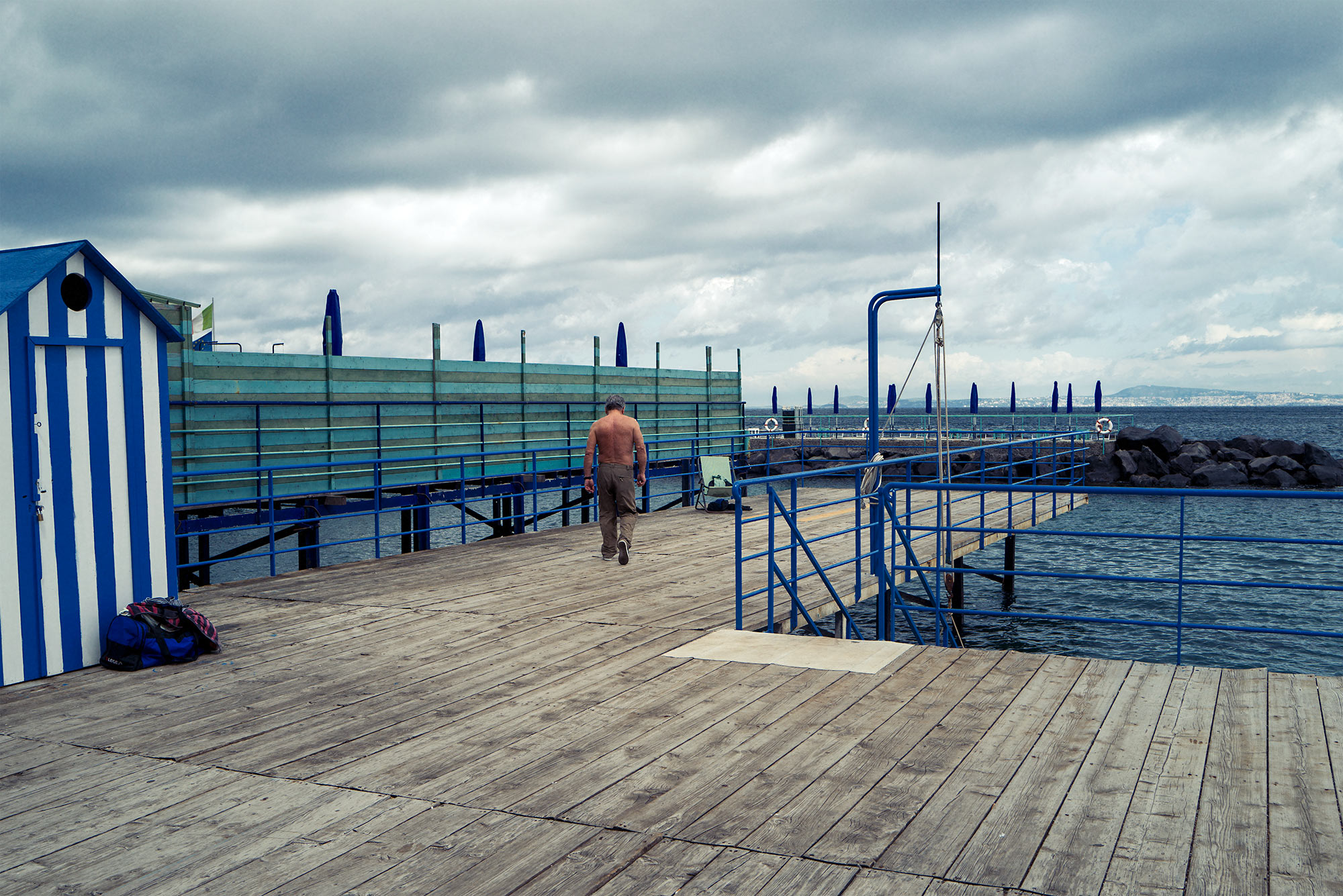 Good Boy Wolf Photographer, filmic portrait,  man walking down decking next to the sea