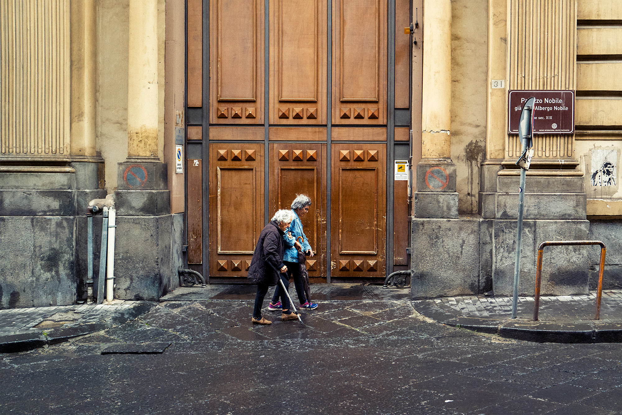 Good Boy Wolf Photographer, filmic portrait,  couple walking past large wooden door