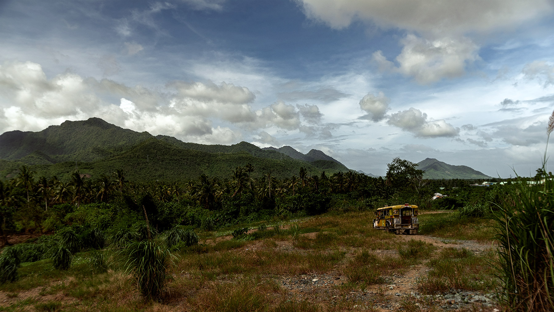 Good Boy Wolf Photographer, filmic landscape, Philippines, mountain filled with tree and a yellow bus