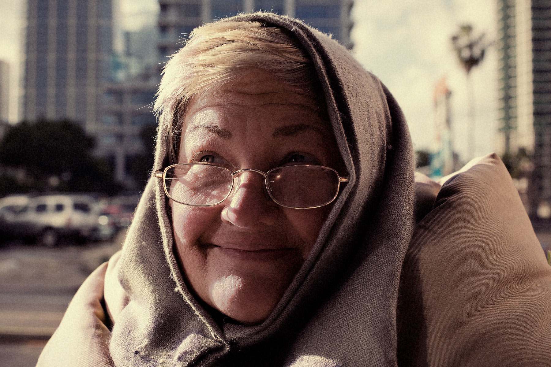 Good Boy Wolf Photographer, filmic portrait, homeless woman wrapped in blankets smiling