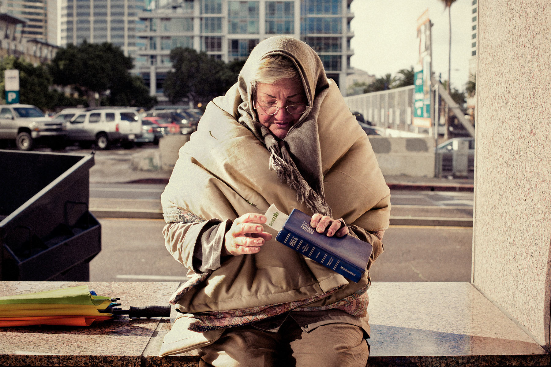 Good Boy Wolf Photographer, filmic portrait, homeless woman wrapped in blankets holding a bible