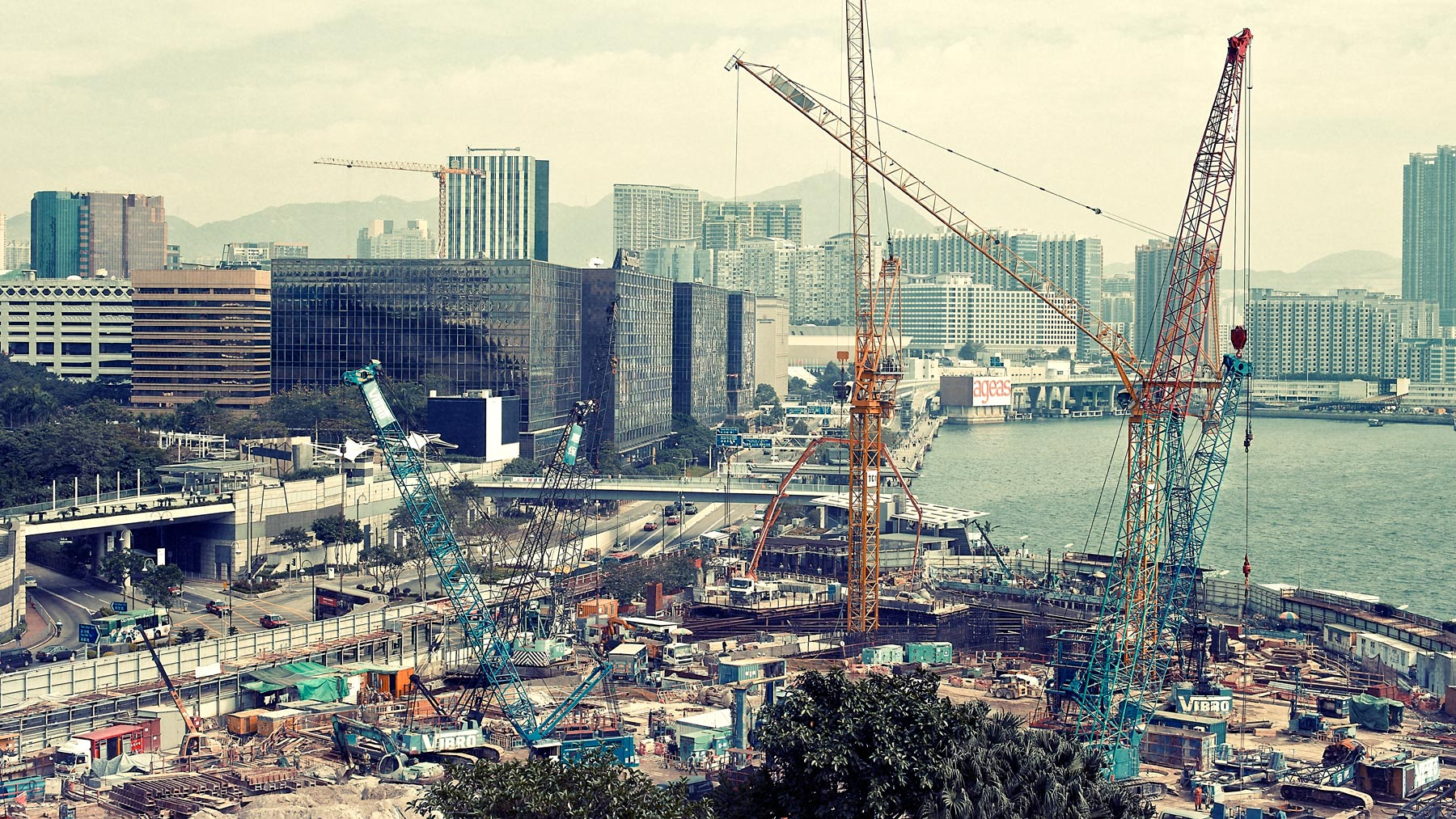 Good Boy Wolf Photographer, filmic landscape, building site in Hong Kong with cranes and building  site