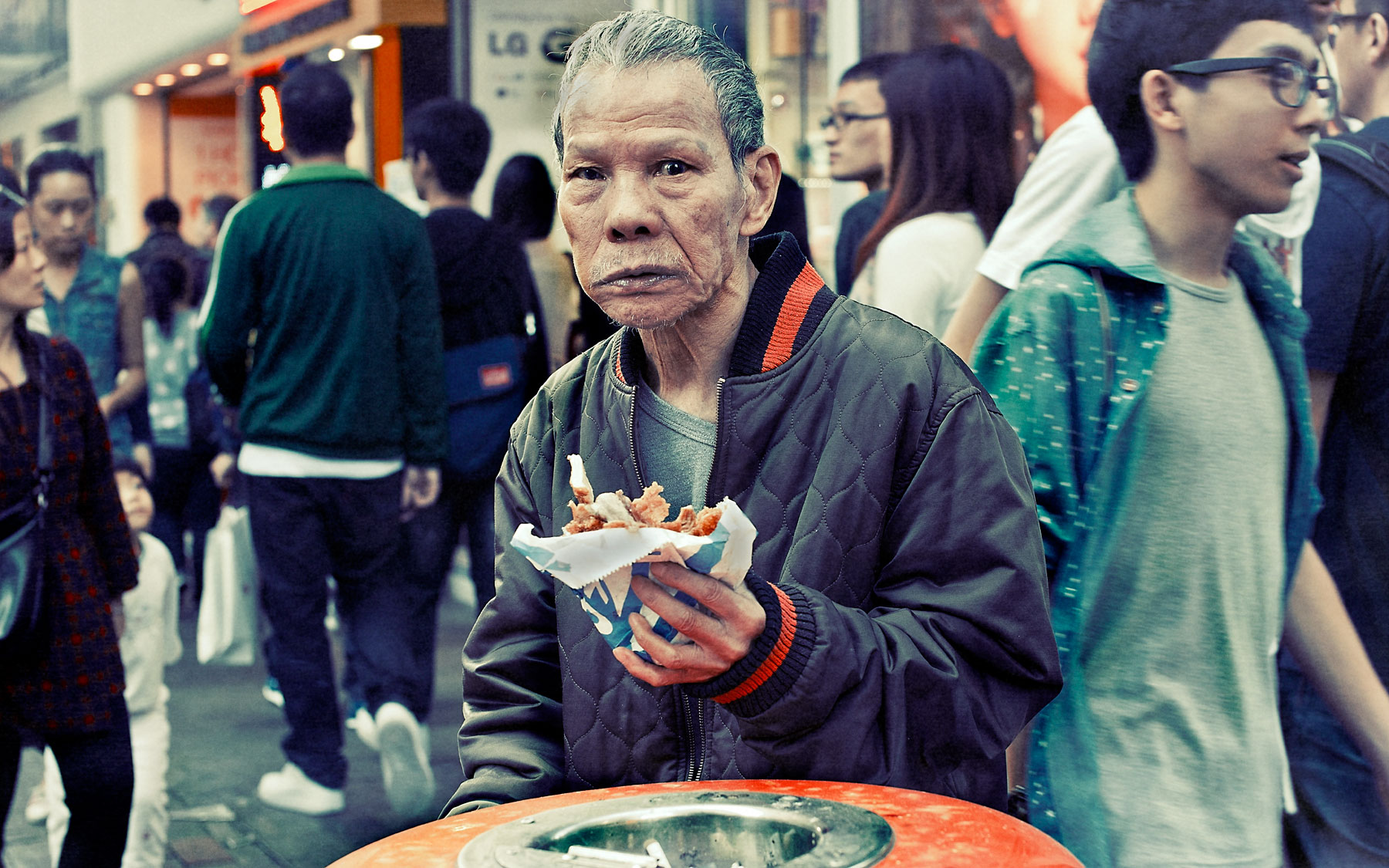 Good Boy Wolf Photographer, filmic portrait, Chinese man eating food out of the bin