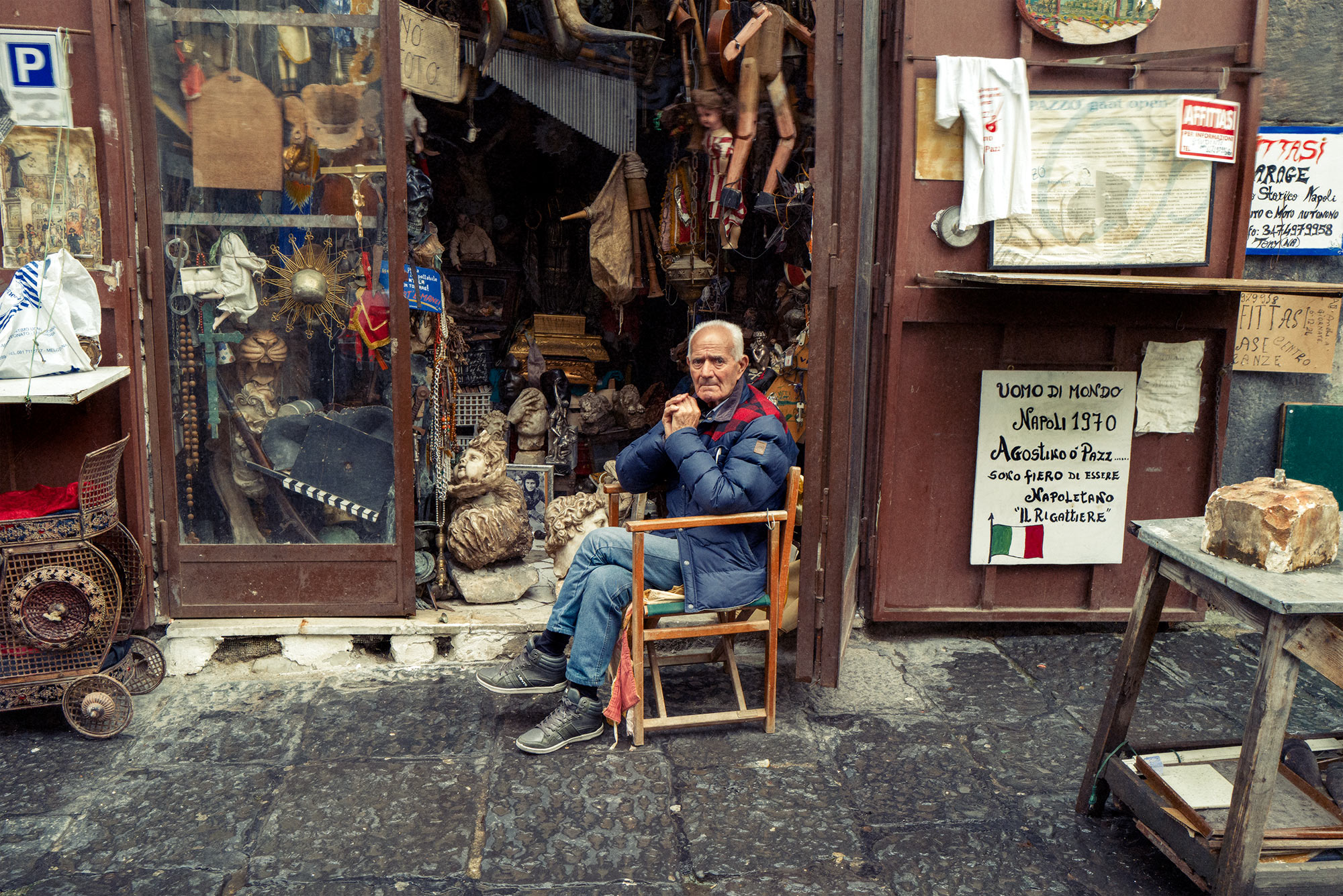 Good Boy Wolf Photographer, filmic portrait, Italian man sitting outside his shop