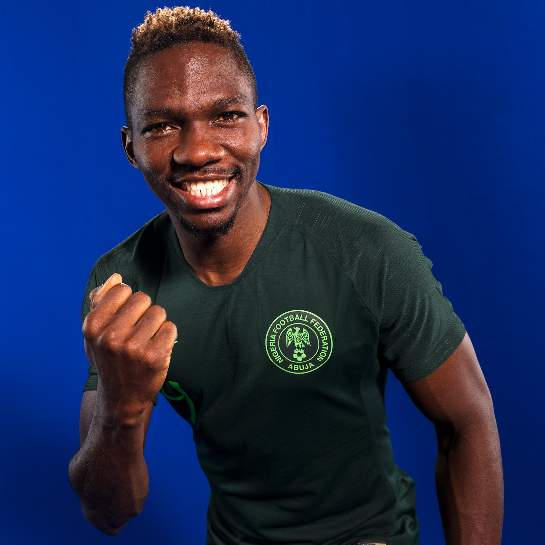 Good Boy Wolf Photographer, filmic portrait,  Nigerian footballer smiling in his green football top