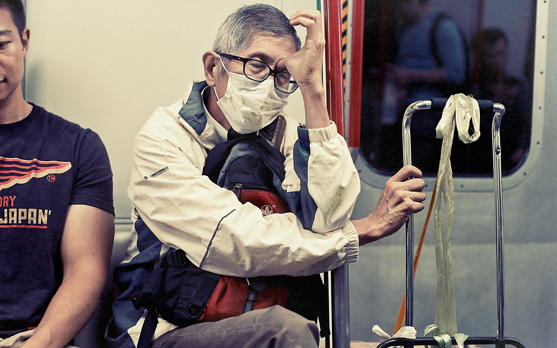 Good Boy Wolf Photographer, filmic portrait, Chinese man asleep on a train wearing a mask