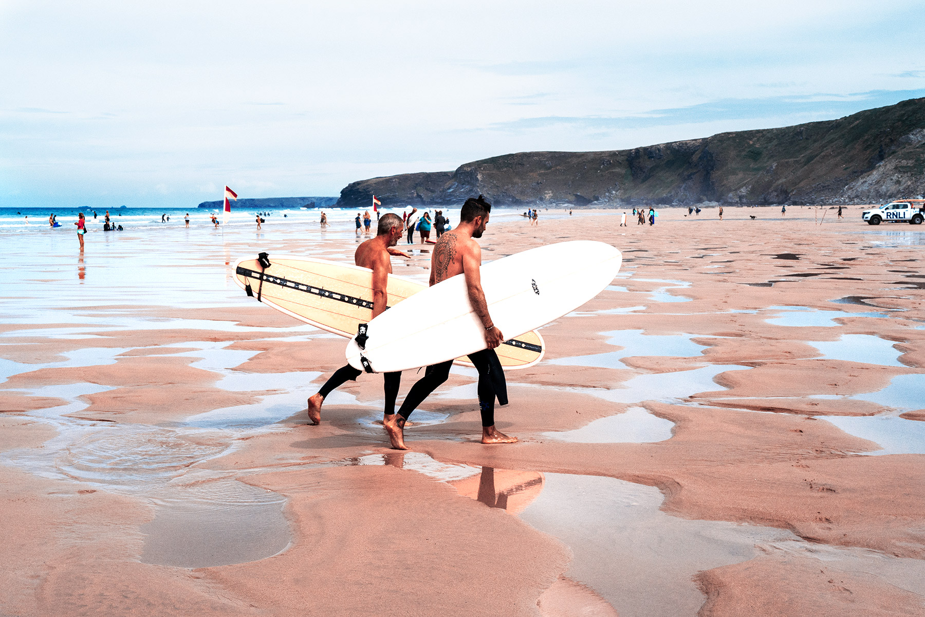 Good Boy Wolf Photographer, filmic portrait, two surfers walking on wet sand