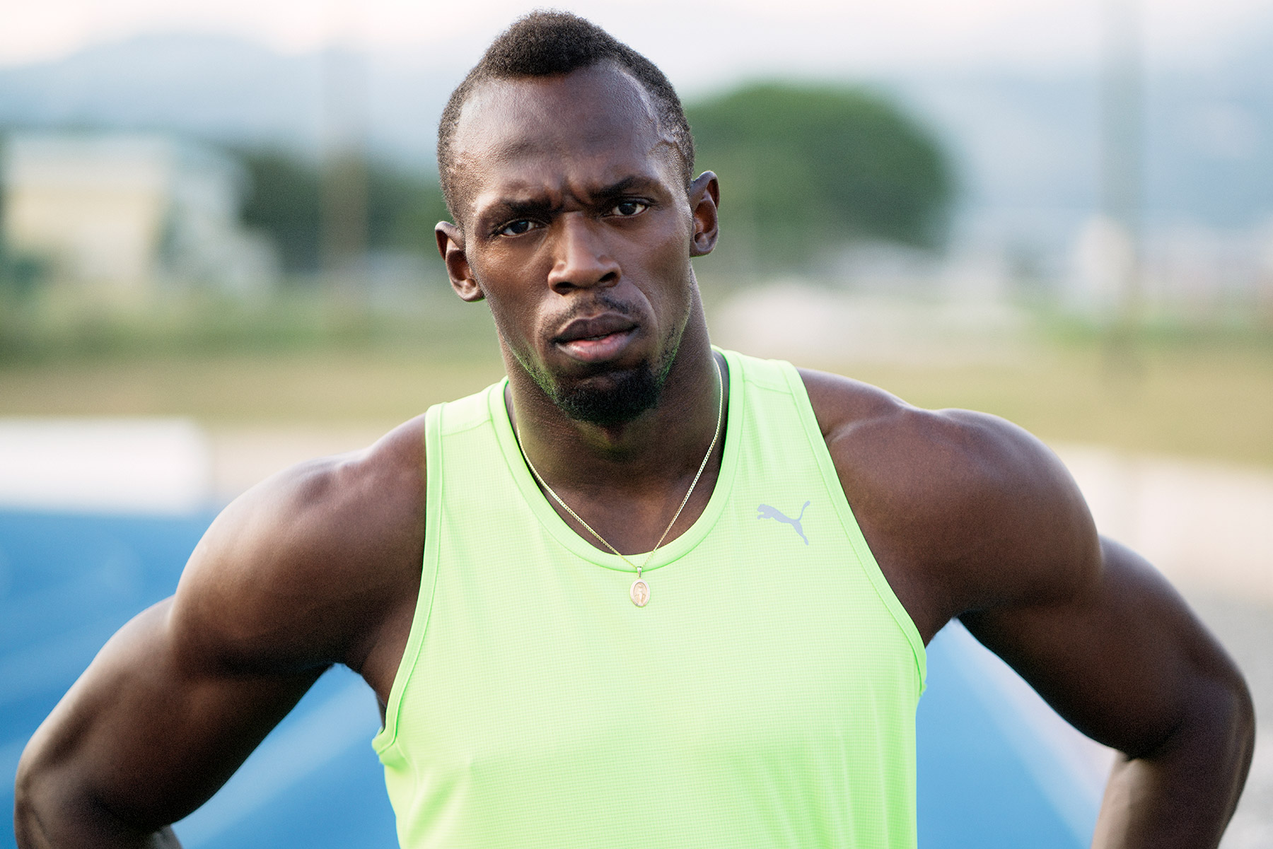 Good Boy Wolf Photographer, filmic portrait,  Usain Bolt runner standing with his hands on hips