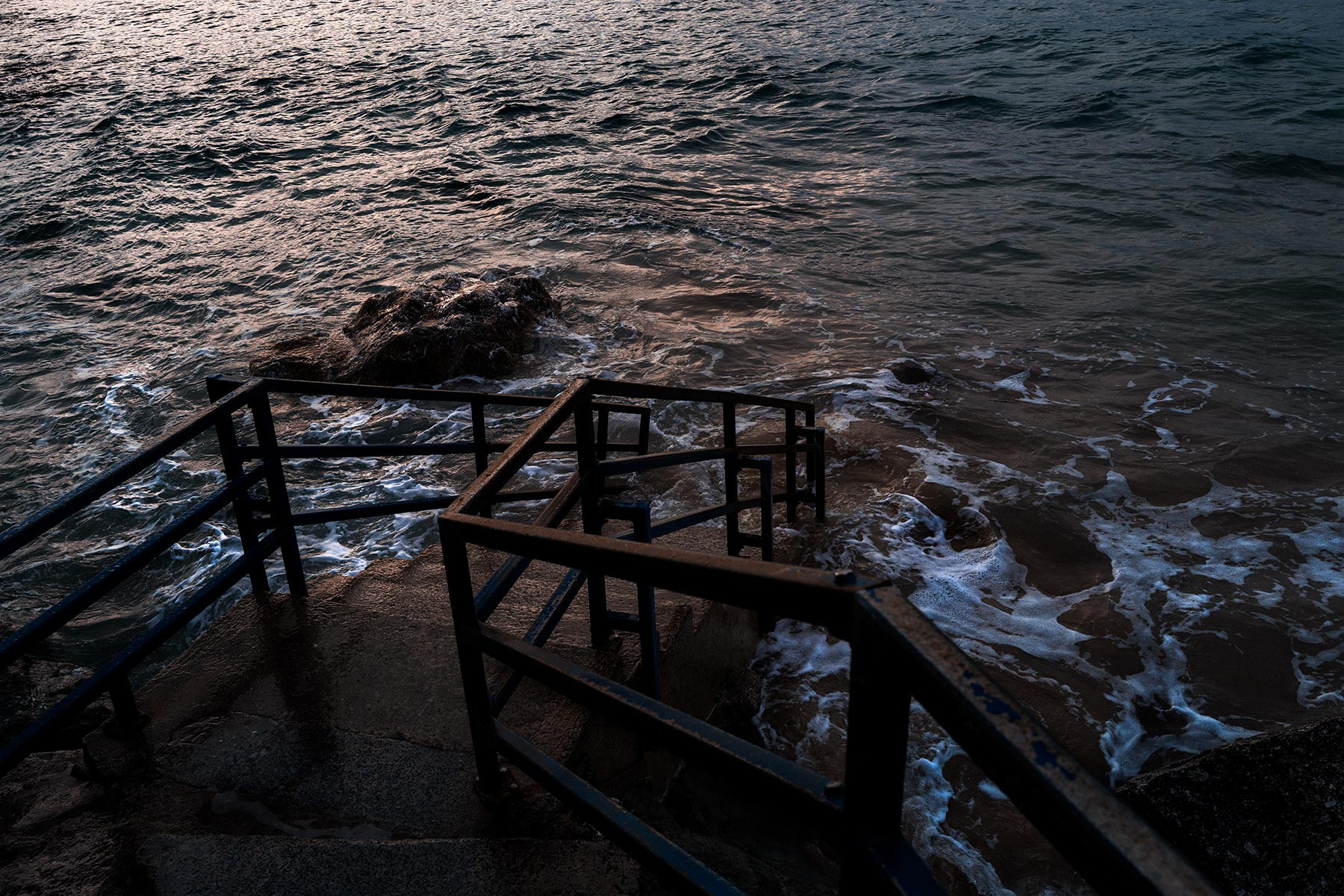 Good Boy Wolf Photographer, filmic landscape,  waves covering stairs in the sea